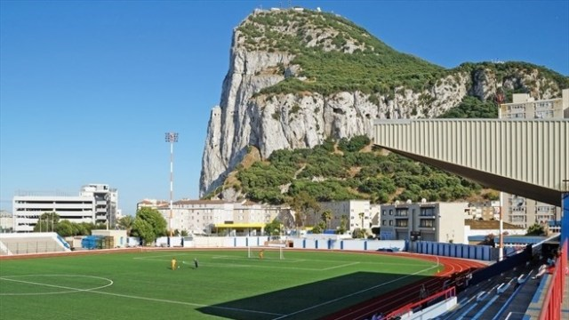 The Rock of Gibraltar overlooks Victoria Stadium, which cannot be used due to its artificial turf. (uefa.com)