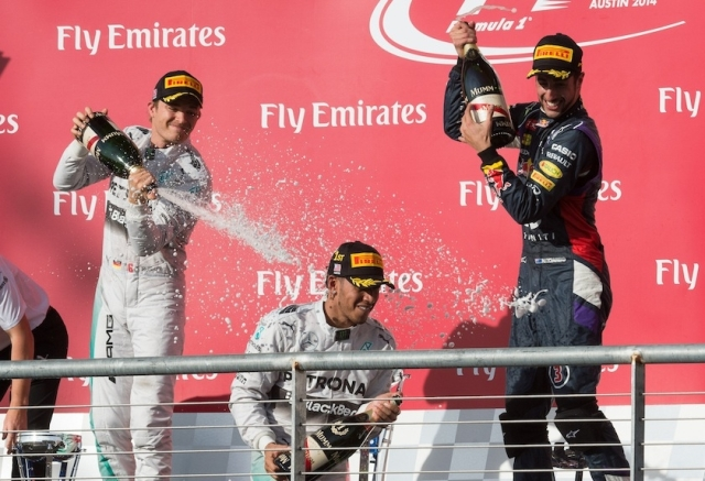 Hamilton (C.) is sparyed by team-mate Rosberg (L.) as third-place Daniel Ricciardo (R.) gets ready to join in.